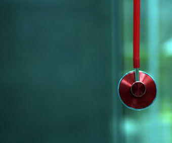 closeup of red stethoscope against blurred blue-green background