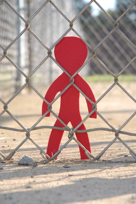 cutout figure behind barbed wire